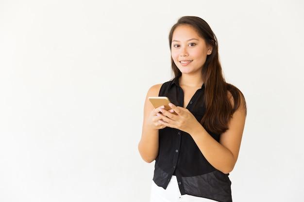Frau, die durch smartphone simst und an der kamera lächelt
