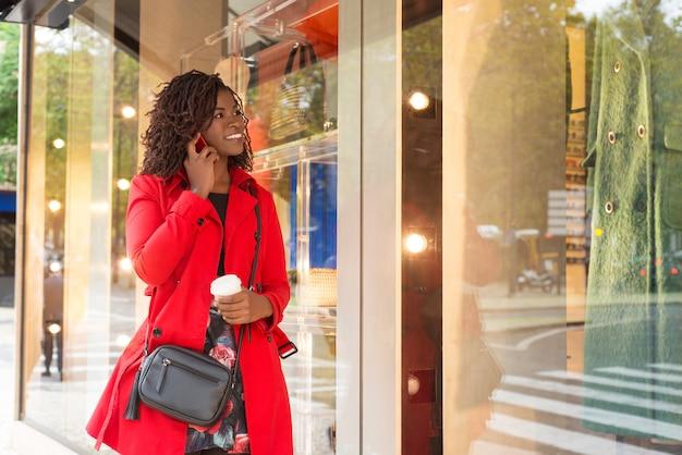 Frau, die durch smartphone spricht und schaukasten betrachtet