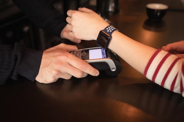 Frau, die durch smartwatch mit nfc-technologie bezahlt