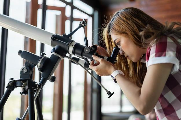 Frau, die durch teleskop schaut