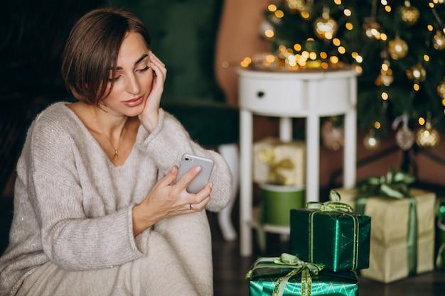Frau, die durch weihnachtsbaum sitzt und am telefon kauft