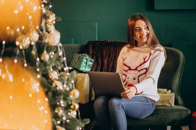 Frau, die durch weihnachtsbaum sitzt und online-verkäufe kauft