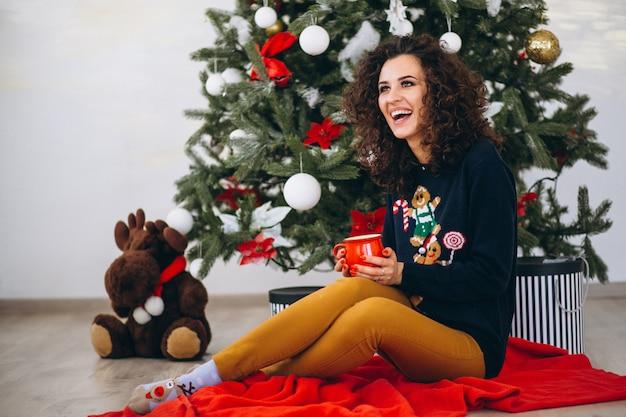 Frau, die durch weihnachtsbaum sitzt und tee trinkt