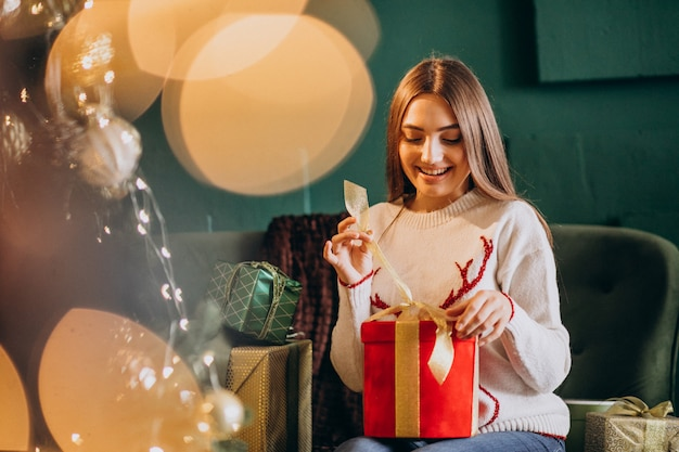 Frau, die durch weihnachtsbaum sitzt und weihnachtsgeschenk auspackt