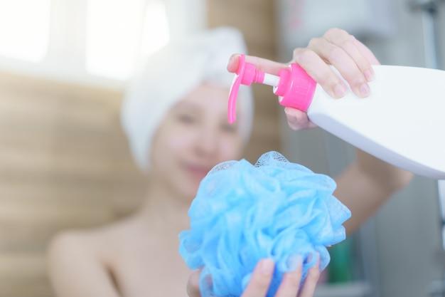 Frau, die duschgel auf puffschwamm gießt, dusche nimmt. hygienekonzept.