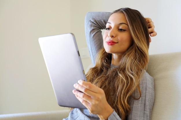 Frau, die e-book auf ihrem tablet-computer liest, sitzt auf einer couch zu hause