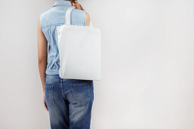 Frau, die eco gewebetaschenisolat auf grauem hintergrund hält