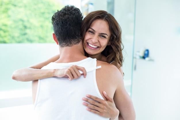 Frau, die ehemann beim halten der schwangerschaftsausrüstung umarmt
