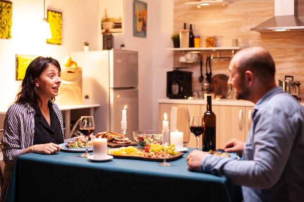 Frau, die ehemann beim romantischen abendessen in der küche überrascht ansieht. reden sie gerne am tisch im speisesaal, genießen sie das essen zu hause und haben sie eine romantische zeit bei kerzenlicht.