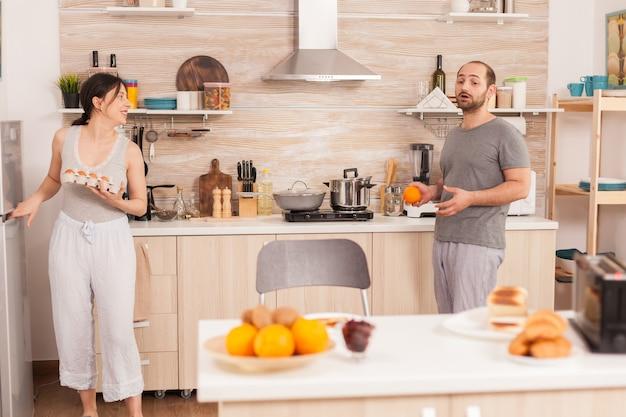 Frau, die eier aus dem kühlschrank nimmt, um frühstück für sie und ihren mann in der küche zu machen. ehemann unterhält sich mit seiner frau, während sie eier zum frühstück zubereitet.