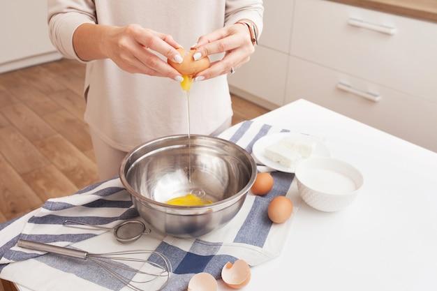 Frau, die eier in schüssel knackt. hände, die ein ei über einer metallschale halten