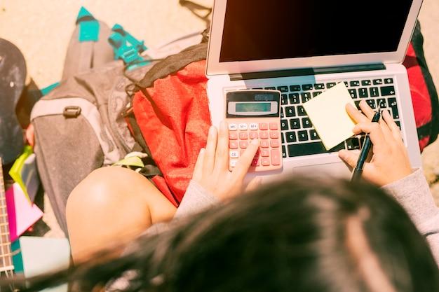 Frau, die eigenhändig kenntnisse mit taschenrechner auf laptop am sonnigen tag nimmt