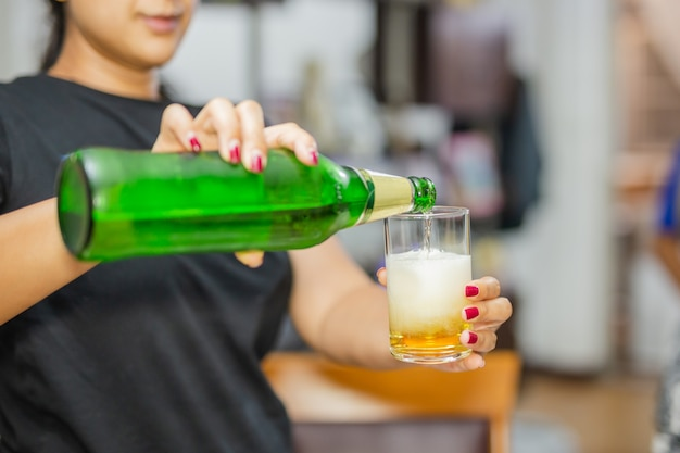 Frau, die ein abgefülltes bier in das glas auf der party gießt.