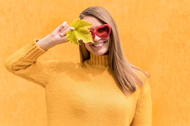 Frau, die ein auge mit einem herbstblatt bedeckt
