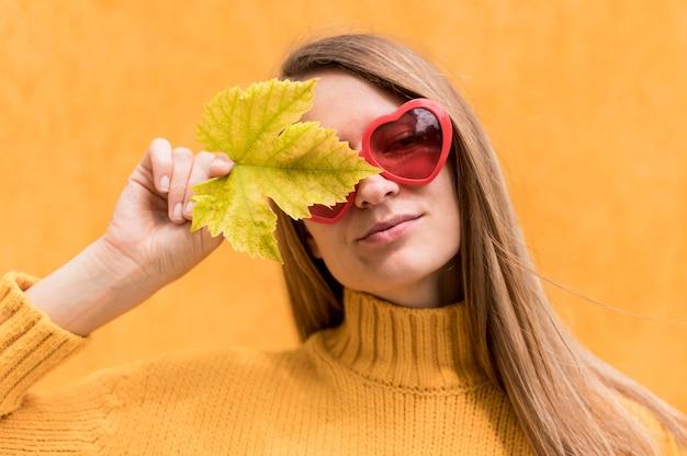 Frau, die ein auge mit einer herbstblatt-nahaufnahme bedeckt