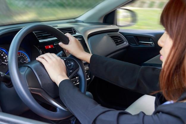 Frau, die ein auto antreibt und auf hupenknopf - transportkonzept drückt.