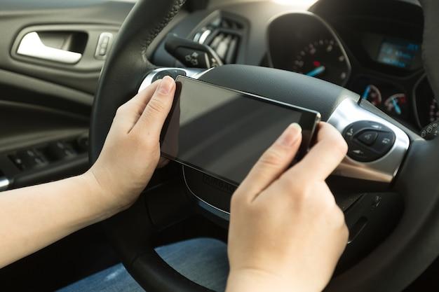 Frau, die ein auto fährt und eine nachricht am telefon schreibt