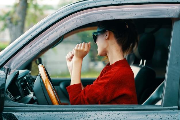 Frau, die ein auto fährt, während es regnet