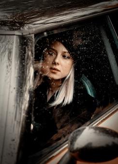 Frau, die ein auto im regen fährt