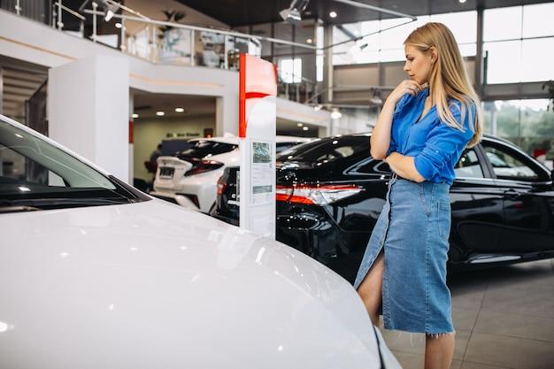 Frau, die ein auto in einem autosalon betrachtet