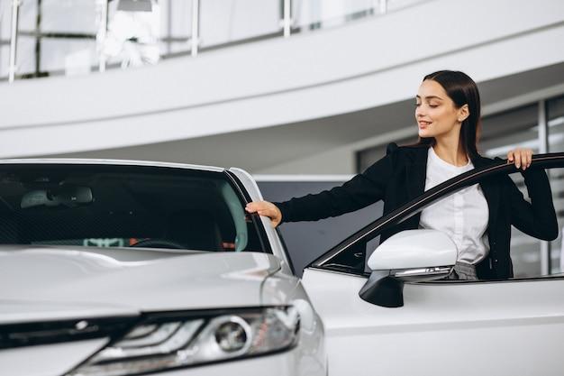 Frau, die ein auto in einem autosalon wählt
