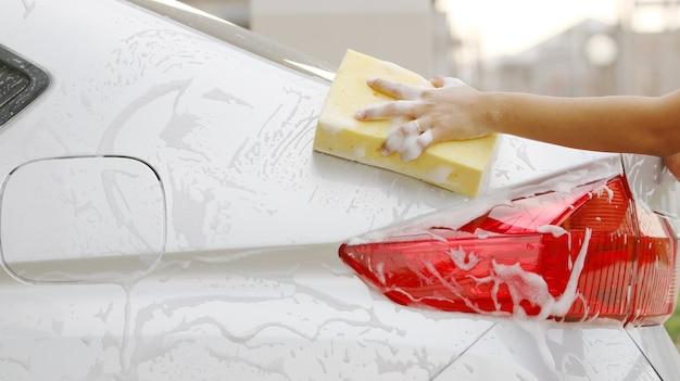 Frau, die ein auto mit einem schwamm und einer seife wäscht