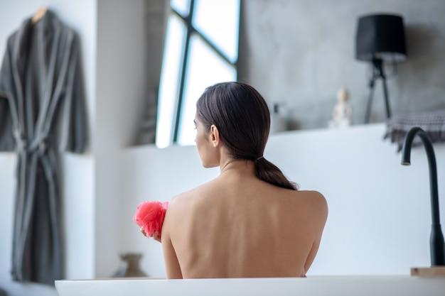 Frau, die ein bad mit einem roten schwamm nimmt