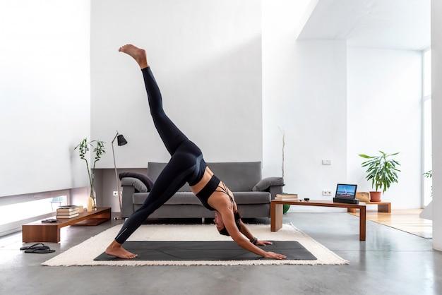 Frau, die ein bein nach unten gerichteten hundensplit unter verwendung des online-yoga-trainingsprogramms in der tablette zu hause tut