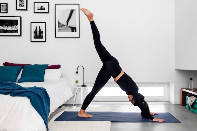 Frau, die ein bein nach unten gerichteten hundensplit während einer yoga-praxis am modernen minimalistischen schlafzimmer tut