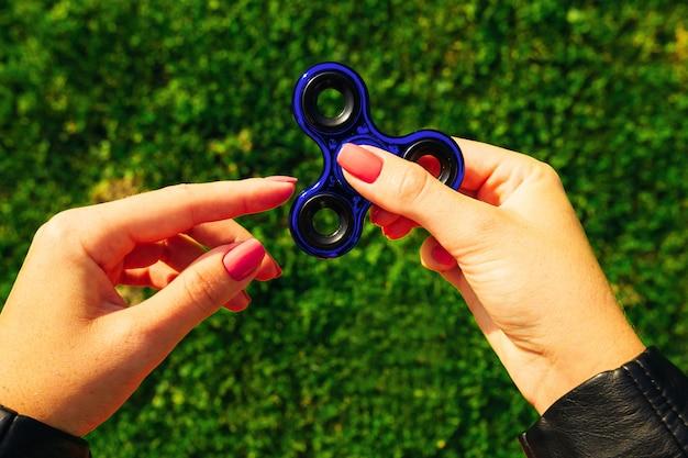 Frau, die ein beliebtes spielzeug auf grünem gras hält