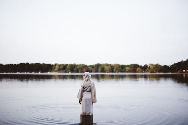 Frau, die ein biblisches gewand trägt, während sie im wasser steht - konzept, das ihre sünden reinigt