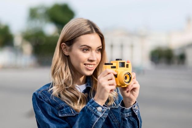 Frau, die ein bild mit gelbem kamera verwischtem hintergrund nimmt