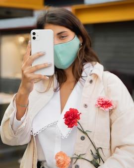 Frau, die ein bild mit smartphone beim halten von blumen macht