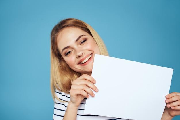 Frau, die ein blatt papier hält, das gegen die blaue wand aufwirft
