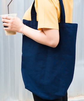 Frau, die ein blaues einkaufstaschemodell trägt