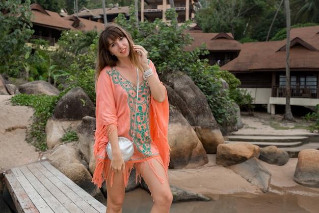 Frau, die ein boho-kleid trägt, das auf dem strand geht. felsen und palmen auf hintergrund. sommermode.