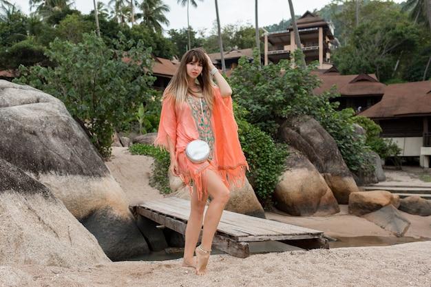 Frau, die ein boho-kleid trägt, das auf dem strand geht. felsen und palmen auf hintergrund. volle länge.