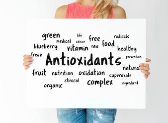 Frau, die ein Brett mit Antioxidansenkonzept hält