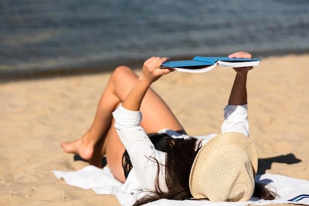 Frau, die ein buch am strand liest