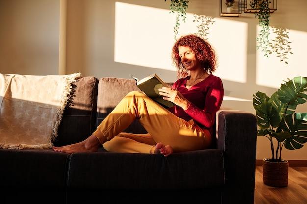 Frau, die ein buch auf der couch während der quarantäne für coronavirus liest - bleiben sie zu hause konzept