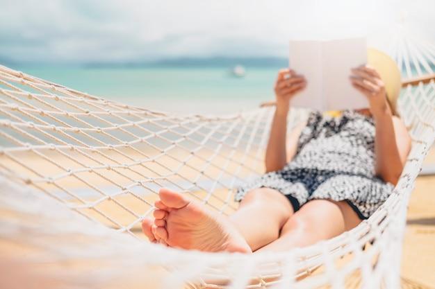 Frau, die ein buch auf hängemattenstrand in den freizeitsommerferien liest