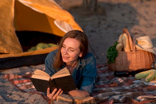 Frau, die ein buch auf picknickdecke liest
