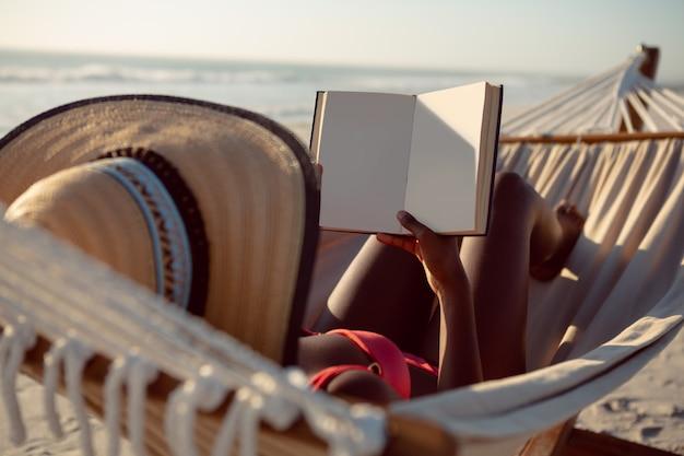 Frau, die ein buch bei der entspannung in der hängematte auf dem strand liest