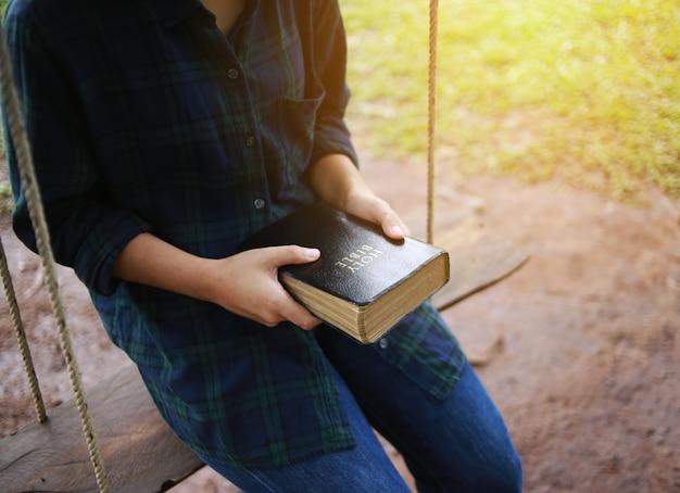 Frau, die ein buch, die bibel, natur hält.