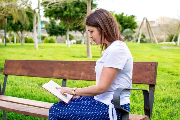 Frau, die ein buch im park liest. linkes exemplar