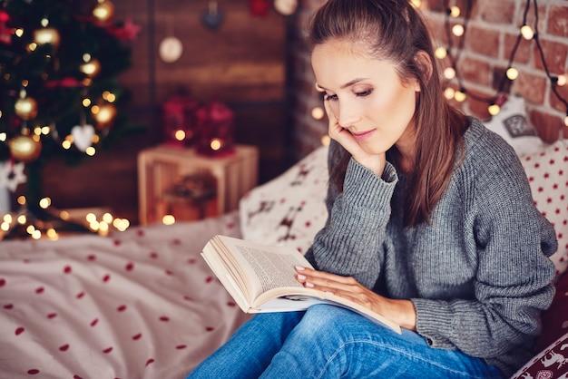 Frau, die ein buch im schlafzimmer liest