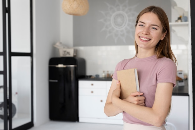 Frau, die ein buch in der küche hält