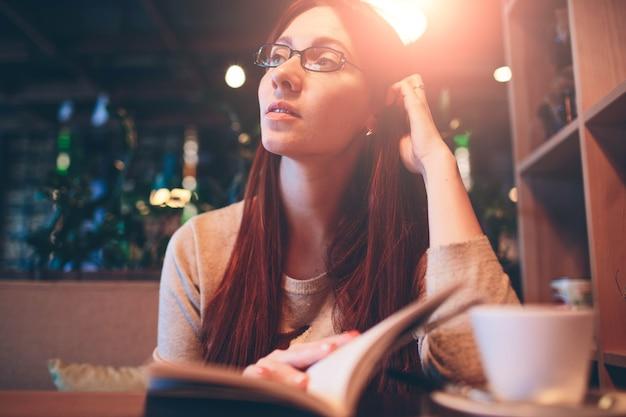 Frau, die ein buch in einem café liest