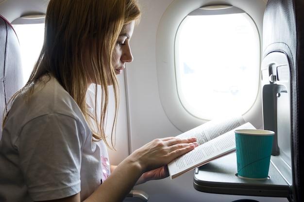 Frau, die ein buch in einem flugzeug liest