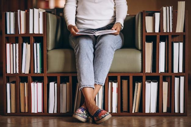 Frau, die ein buch in einem stuhl liest